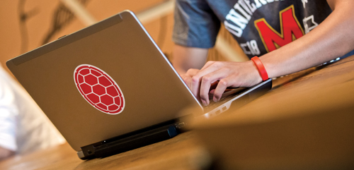 Student on Laptop with UMD Shell Sticker