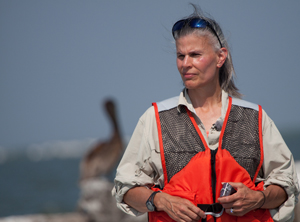 Wildlife Conservationist, Schlyer, in a high-visibility vest with a waterfront background