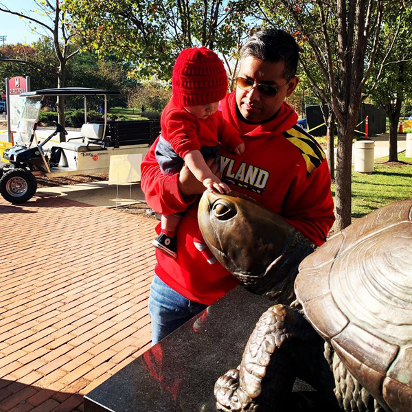 adult holding toddler in their arms. the toddler is reaching out with one had to touch the nose of Testudo in front of the Riggs Alumni Center