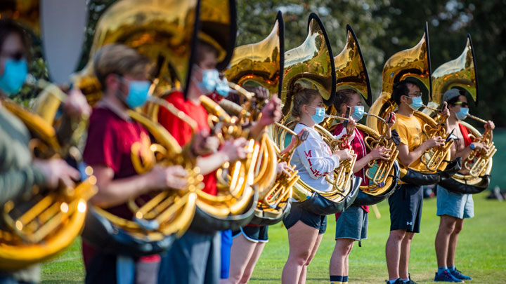 Sousaphone players for the Mighty Sound of Maryland marching band practicing on Chapel Field, with masks, on a fall afternoon on October 9, 2020.