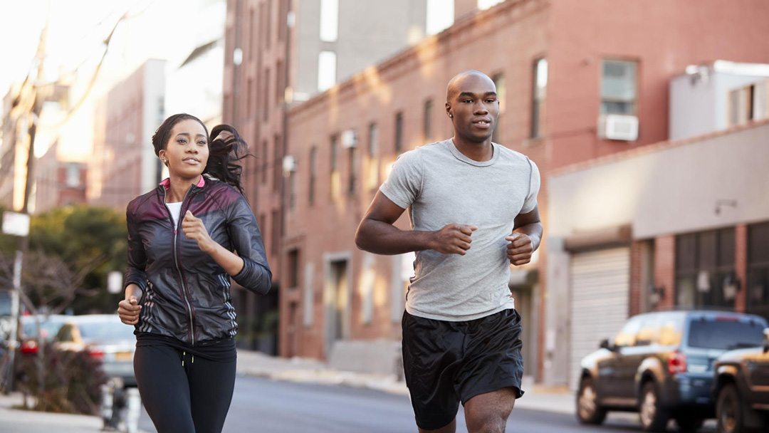 Two individuals in running close jogging down an urban street. The background is artfully out of focus.