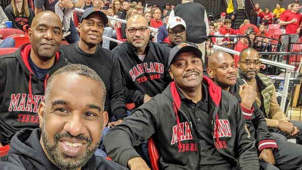 Group of people sitting in the stands at a UMD basketball game. A few individuals are wearing black UMD branded zip up hoodies