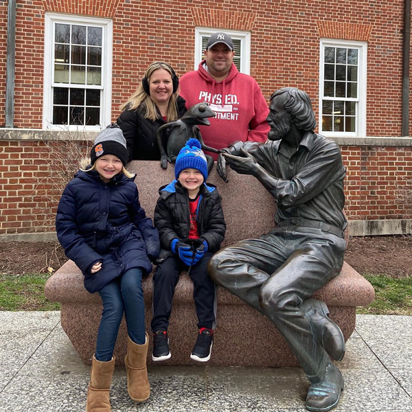Two adults stand behind the bench of the Jim Henson monument on campus, two kids sit on the stone bench next to the statue of Jim Henson