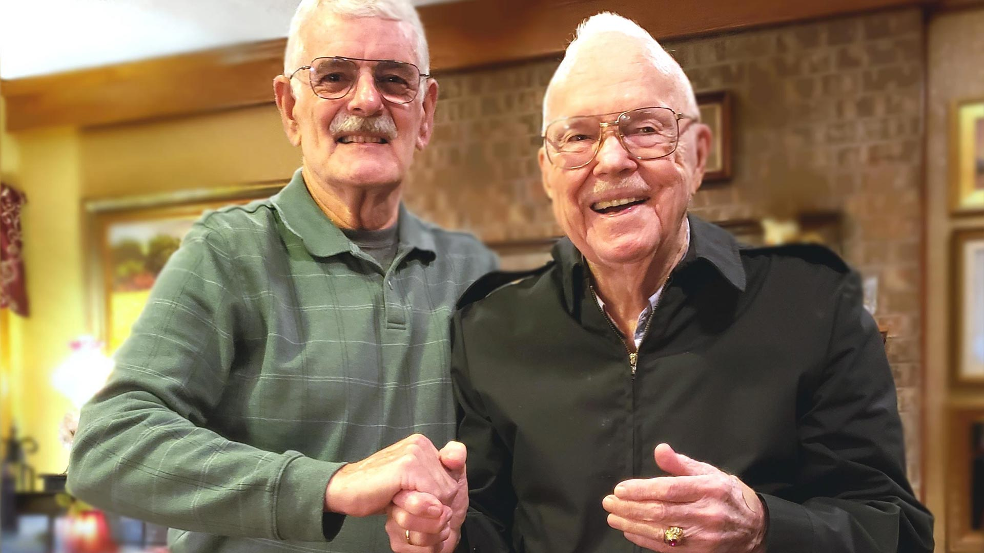 Two individuals standing facing camera holding hands smiling
