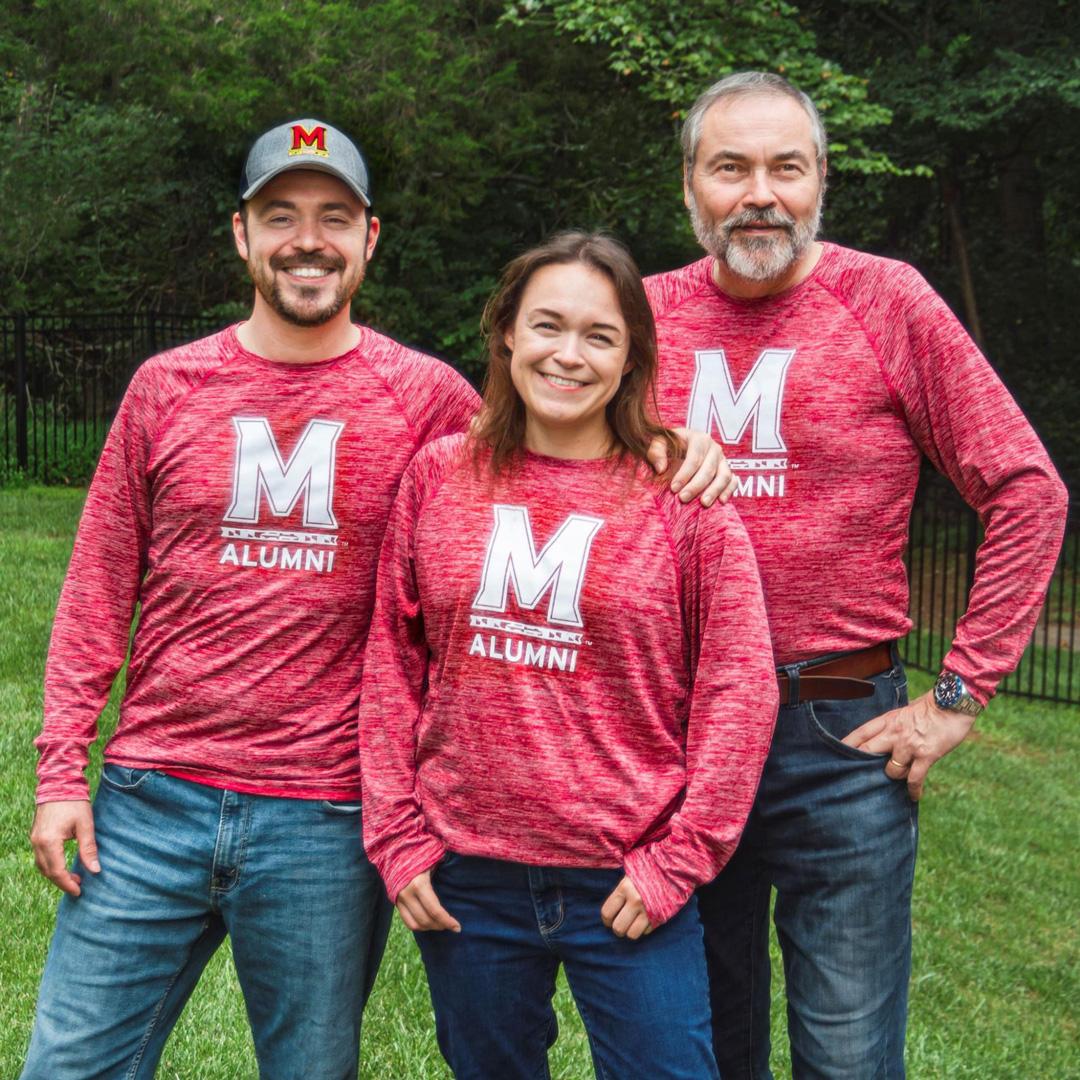 Alumni Association members posing with their red, long sleeve alumni shirts