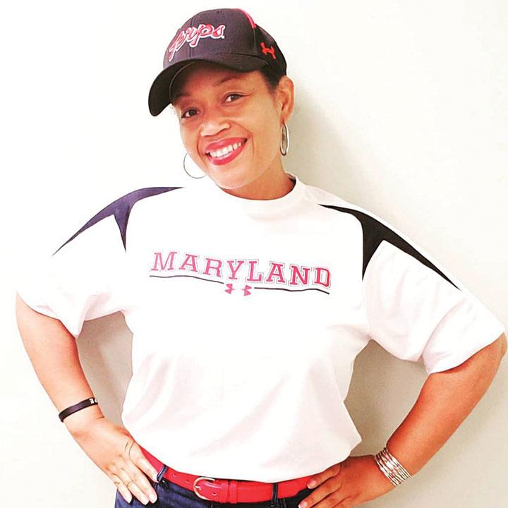Wynné Briscoe wearing a UMD shirt and baseball cap