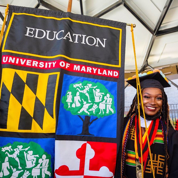 Alysa Conway holding an Education Graduation Banner for the university of Maryland in their graduation robes