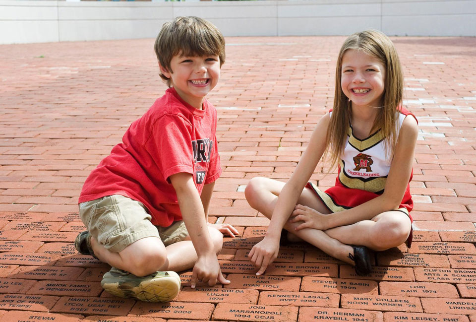 Kids posing with Bricks at the Samuel Riggs IV Alumni Center