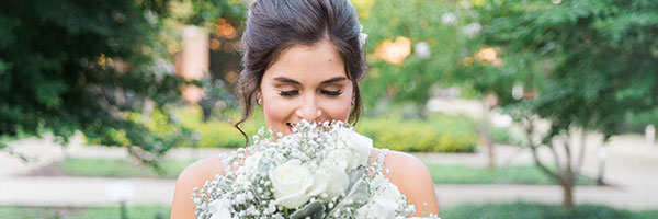 Bride posing with flowers outside of the Samuel Riggs IV Alumni Center