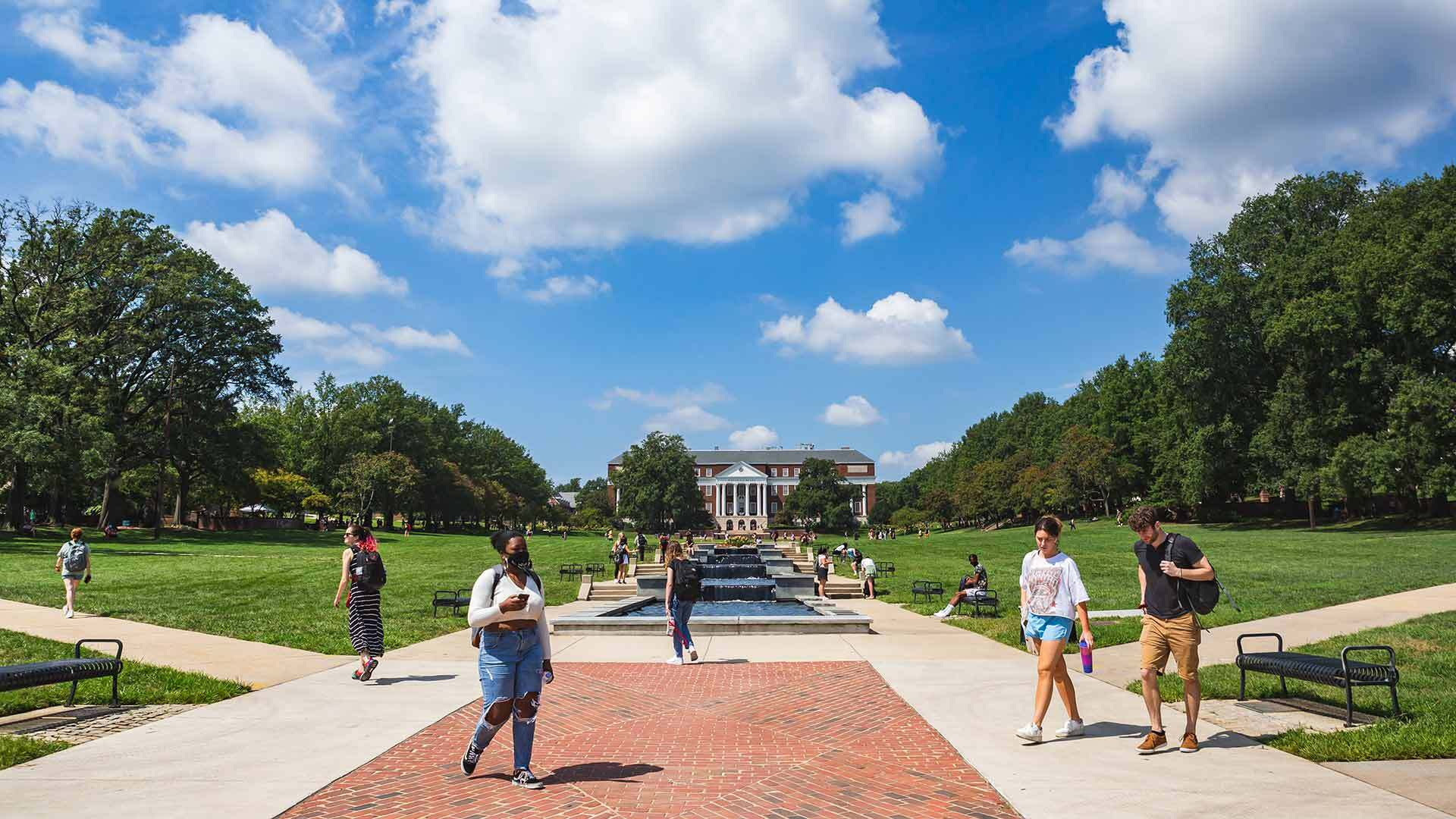 Students walking through McKeldin Mall on a sunny, partially cloudy day