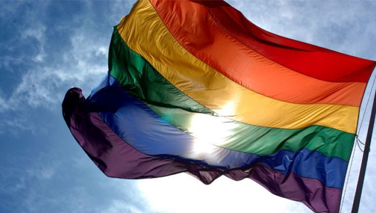 Rainbow Pride flag with a blue sky and the sun shining through its color bands